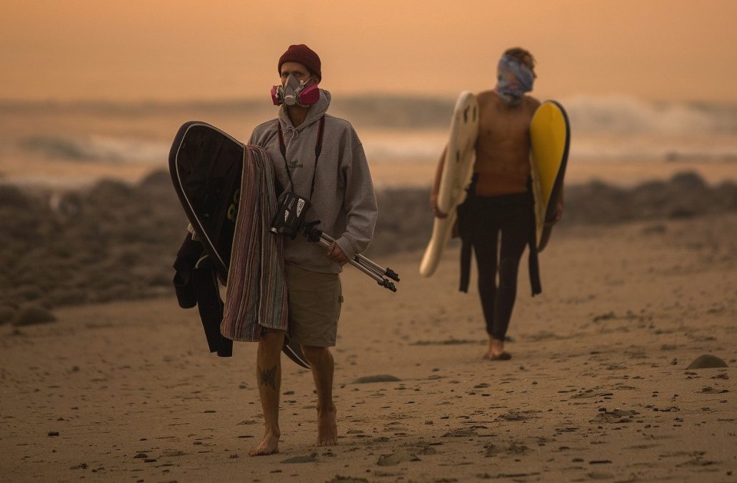 Surfers walk along the coastline wearing masks to keep smoke and ash out from the Thomas fire.