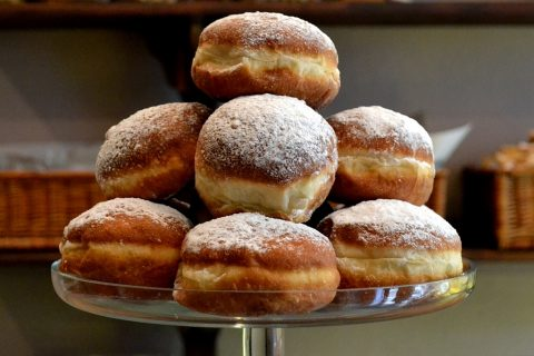 A plate full of paczki donuts.