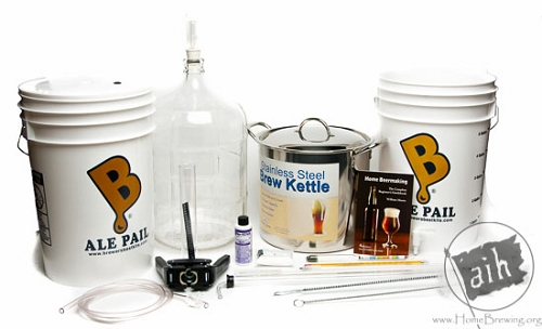 A collection of homebrewing equipment including a steel kettle and carboys.