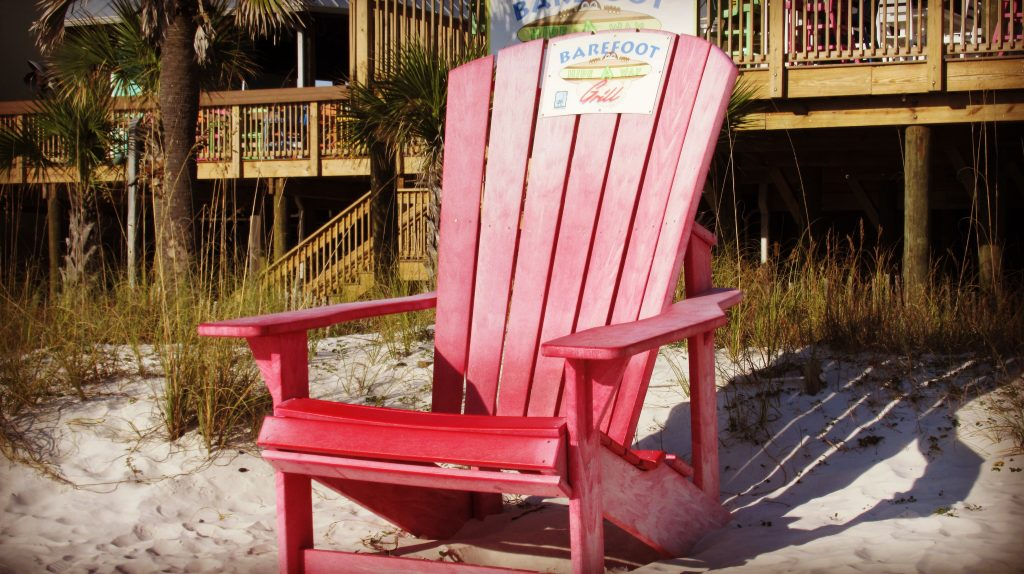 A red chair on the sand outside Barefoot on the Beach restaurant.