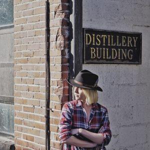 Kristen leaning against the jack Daniels distillery building
