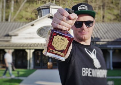 Andrew holds up a bottle of jack Daniels Whiskey